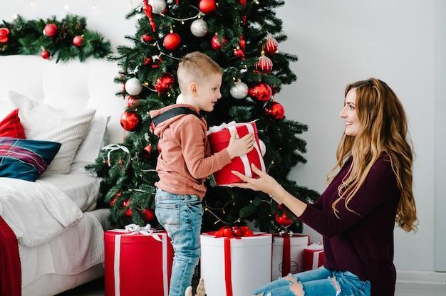 Мама дарит сыну подарок возле елки концепция семейного праздника