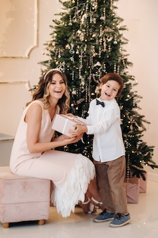 Mom gives her son a christmas present near the christmas tree.happy family.
