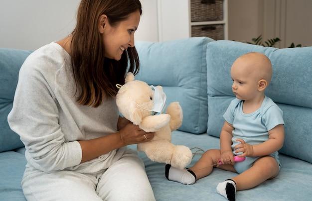 Мама дает ребенку плюшевого мишку с медицинской маской