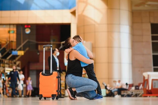Мама встречает сына в аэропорту с чемоданом