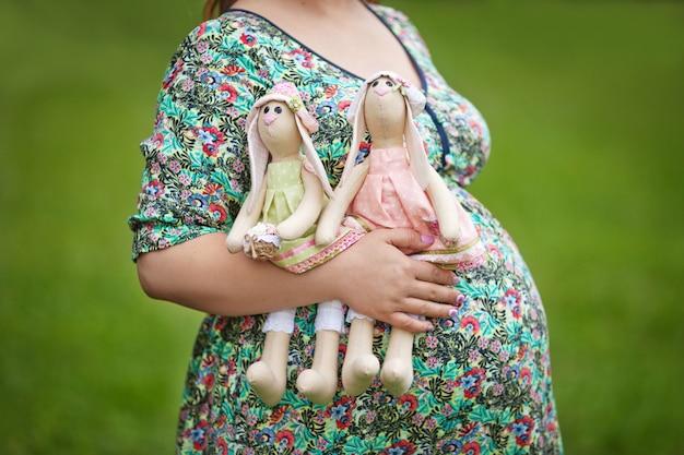 Мама руки держит двух кроликов. живот беременной женщины. двойняшки