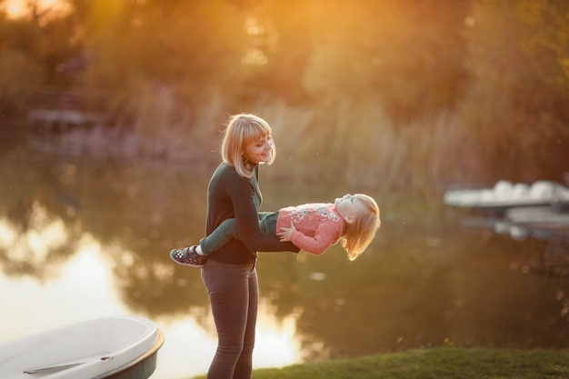 Mom having fun with her daughter near the lake in the autumn on the background of sunset rays