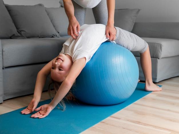 Мама помогает девочке тренироваться на мяче