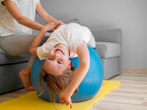 Mom help girl to train on ball
