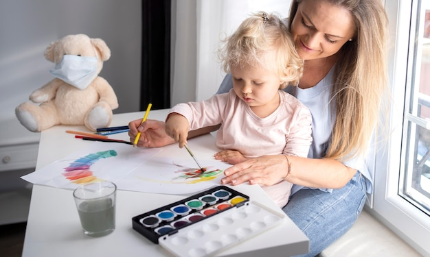 Mom helping child painting at home