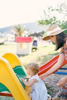 엄마는 어린 소녀가 놀이터에서 미끄럼틀을 오르도록 도와줍니다.