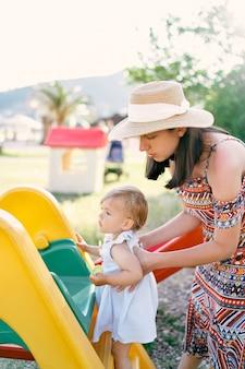 엄마는 어린 소녀가 미끄럼틀을 오르도록 도와줍니다.
