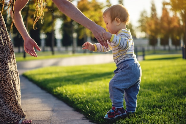 Mom helps cute baby walking on a green lawn in nature on a sunny autumn day