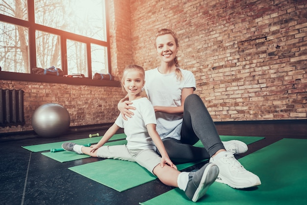 Mom helps daughter to sit on twine in the gym.