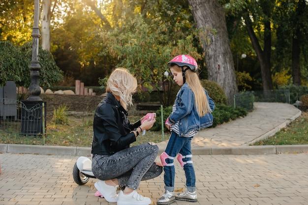 Мама помогает одеть экипировку и шлем своей маленькой дочери для прогулки на сигвее по парку. счастливый семейный отдых.