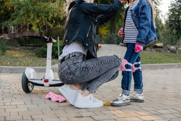 엄마는 공원에서 세그웨이 타기를 위해 어린 딸의 장비와 헬멧을 차려 입는 것을 도와줍니다.