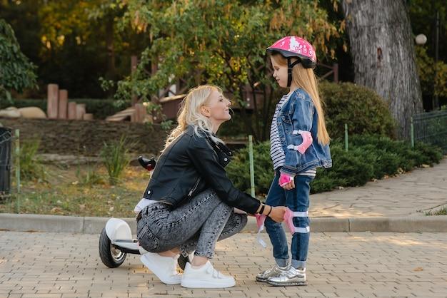 ママは公園でセグウェイに乗るために彼女の小さな娘のギアとヘルメットをドレスアップするのを手伝います