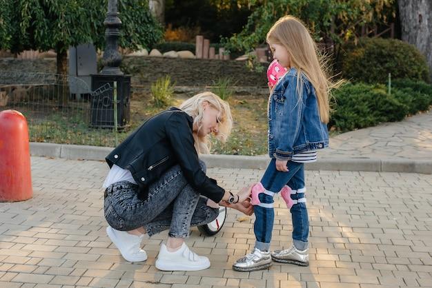 ママは公園でセグウェイに乗るために彼女の小さな娘のギアとヘルメットをドレスアップするのを手伝います。