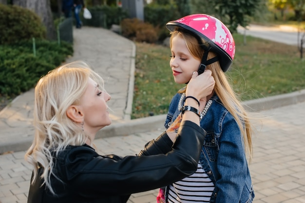 Mom helps dress up her little daughter's gear and helmet for a segway ride in the park