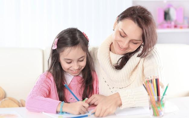 Мама помогает маленькой дочке нарисовать картину.