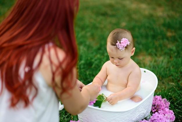 Мама помогает своей годовалой дочке искупаться в ванной.