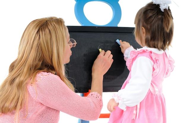 ママは幼稚園の娘が黒板にチョークで描くのを手伝います