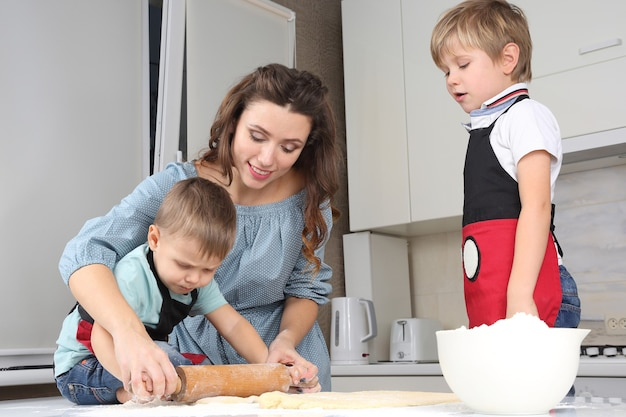 Mom helps young sons knead the dough on the kitchen table