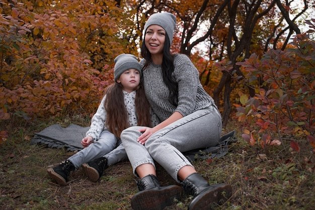 Mom and her 4 years old daughter spending weekend, picnic in the autumn forest together. mother and child relations.