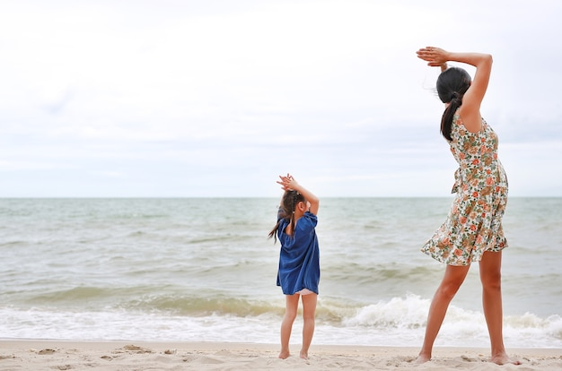 Mom and her child are doing yoga exercises at the beach