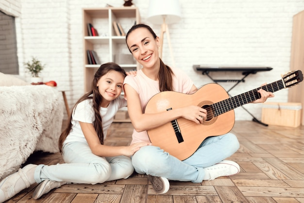 Mom and her daughter are sitting on the floor with guitar.