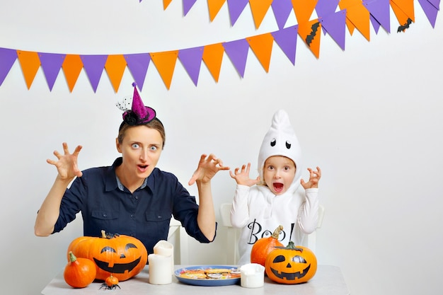 Mom and her daughter make angry faces celebrating halloween. white background wth colored flags