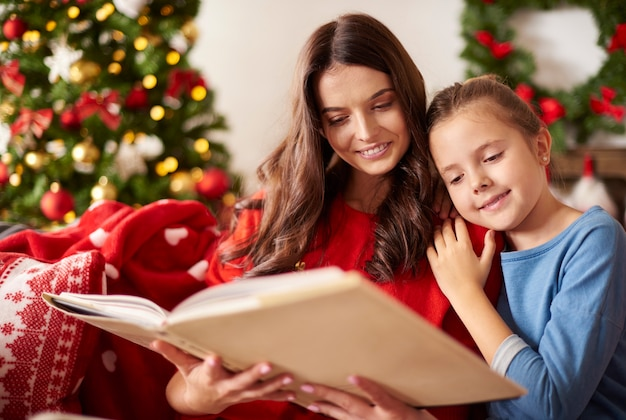 Mom and her daughter reading a book at christmas