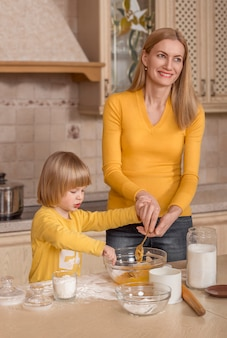 Mom and her little child are cooking in the kitchen.