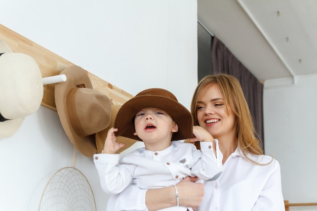 Mom and her little son are having fun, trying on different hats