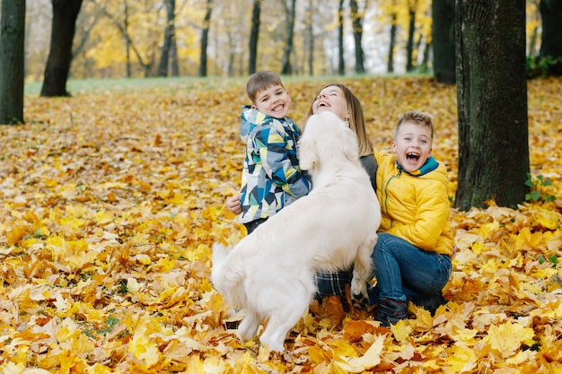 Mom and her sons play with a dog in the park in autumn