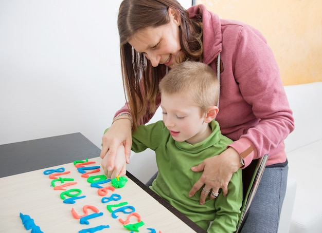 A mom and her young boy play with colored modeling clay