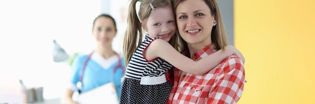 医者の予約で彼女の腕に小さな女の子を保持しているお母さん