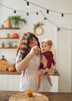ママは女の赤ちゃんを抱いて、キッチンでマッシュポテトのピューレを食べます
