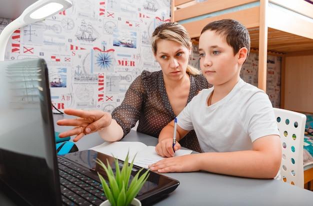 ママはラップトップを持って、画面で息子に手を見せます。若い女性と男の子の机で。ホームスクーリング、遠隔学習。