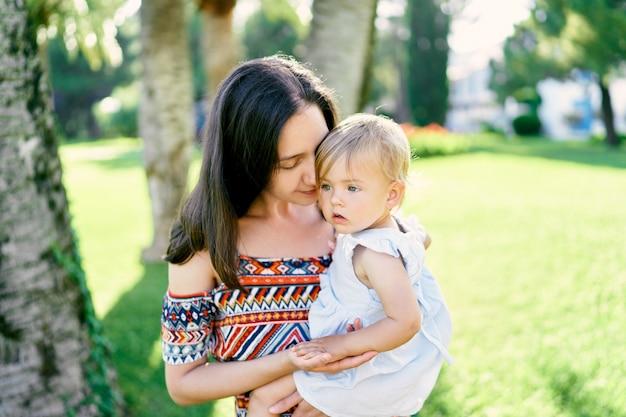 ママは小さな女の子を腕に抱き、クローズアップを抱きしめます