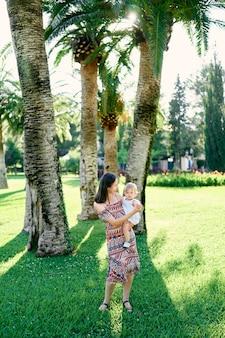 ママはヤシの木の下に立っている彼女の腕の中で小さな女の子を保持しています