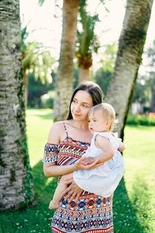 ママはヤシの木の肖像画の下で彼女の腕に小さな女の子を保持します