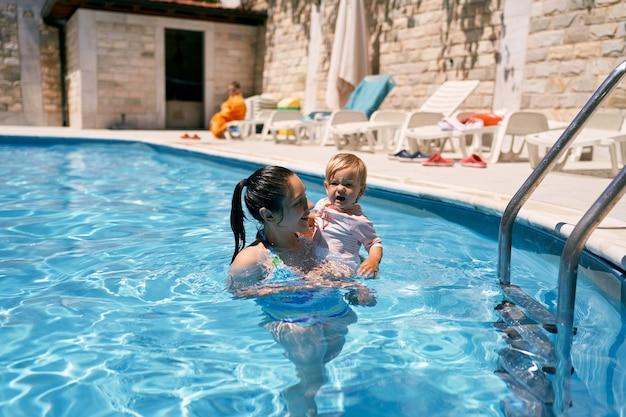 엄마는 수영장에서 팔에 작은 훌쩍이는 소녀를 안고 있다