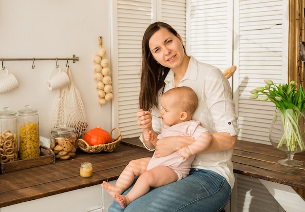 Mom holds a baby girl in her arms and feeds her mashed with a spoon in the kitchen