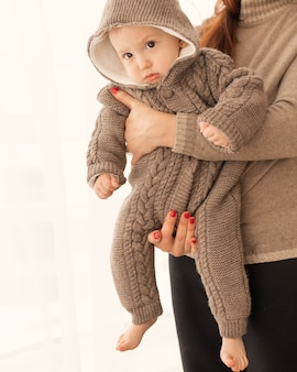 Mom holds a baby in warm knitted jumpsuit on white background