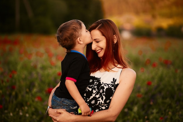 Mom holds charming little son standing on the green field with poppies