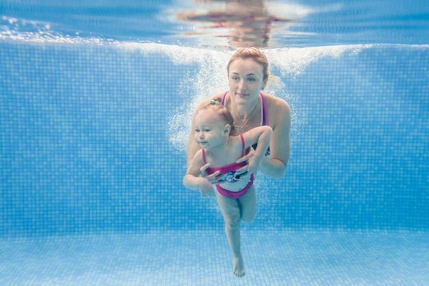 Мама держит дочь погружены в воду, плавают под водой в детском бассейне. дайвинг, малыш. обучение ребенка плаванию. молодая мать или инструктор по плаванию и счастливая маленькая девочка.