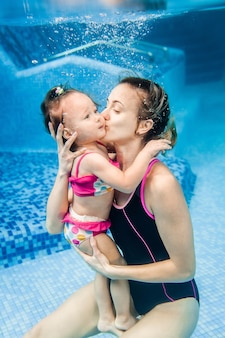 Mom holds daughter are immersed in water, swimming under water in paddling pool. diving baby. learning infant child to swim. young mother or swimming instructor and happy little girl.