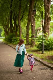 母は雨の後、公園で彼女と一緒に歩いている娘の手を保持しています