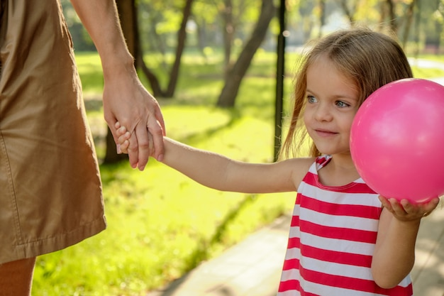 Mom holds the hand of a little girl with a balloon in the park