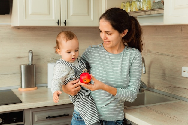 Mom holds her baby in her arms in the kitchen. mom gives an apple to the child.