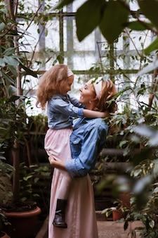 ママは娘を腕に抱えて見ます。幸せな家族。戸外を歩いています。母の日、子供の保護。
