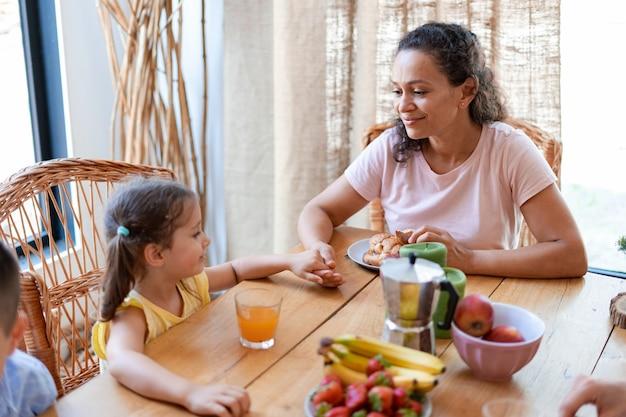 Мама держит дочь за руку и внимательно слушает ее рассказы во время семейного завтрака с фруктами и круассанами.