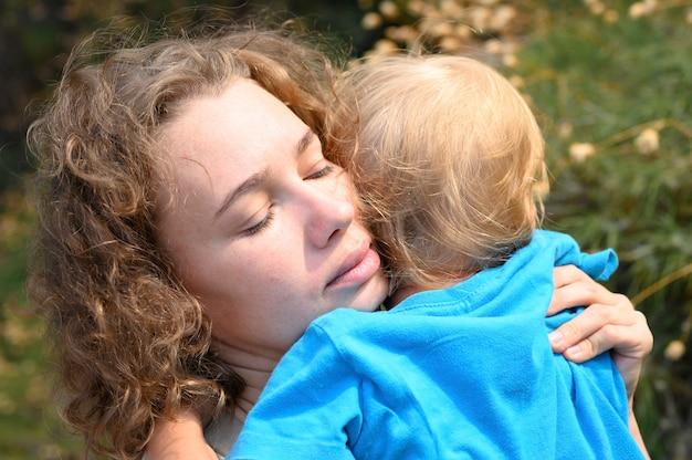 ママは小さな男の子を腕に抱き、ごめんなさい、子供は母親を抱きしめ、彼女に寄り添います