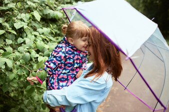 Mom holds her little daughter on hands standing under umbrella in the park